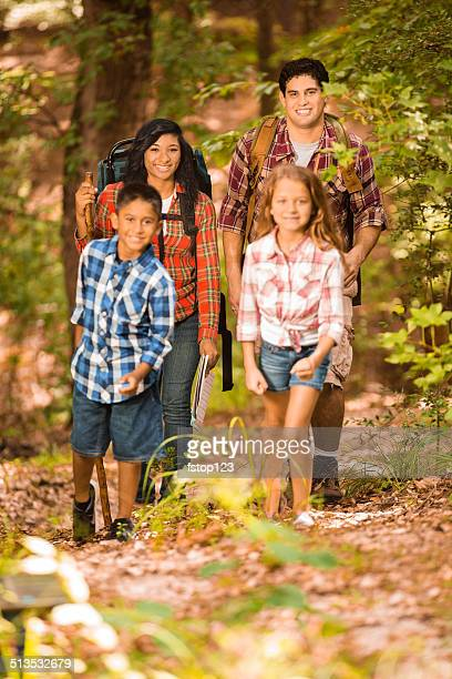 Multi-ethnic family hiking, backpacking outdoors in national park area.