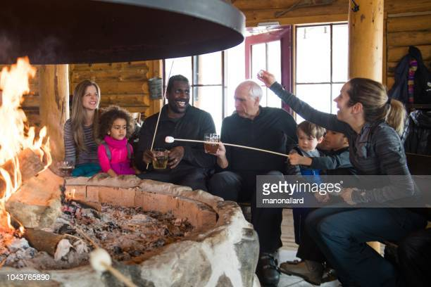 multi-ethnic family in a ski cottage, apres-ski break - apres ski stock pictures, royalty-free photos & images