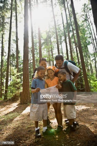 multi-ethnic family looking at map in woods - lane sisters stock photos and pictures