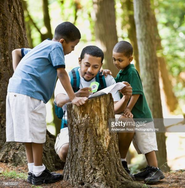 Multi-ethnic family looking at map in woods