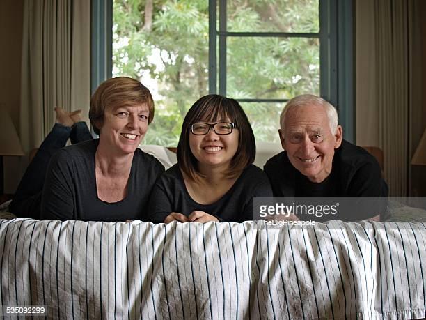 Multiethnic family of three on bed facing camera