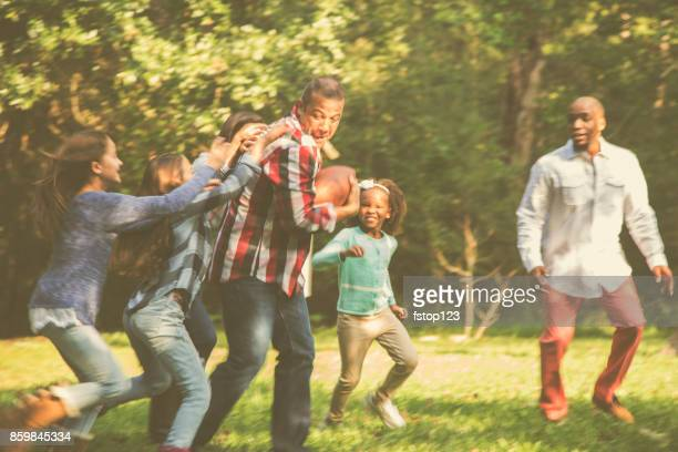 multi-ethnic family playing football in backyard at thanksgiving. - african american ethnicity photos stock photos and pictures