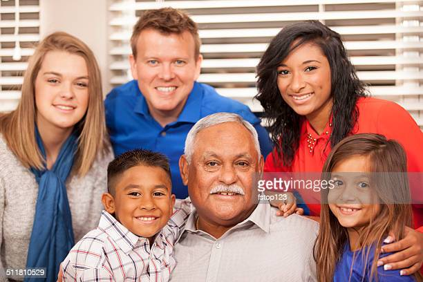 Multi-ethnic family posing with grandfather for picture.