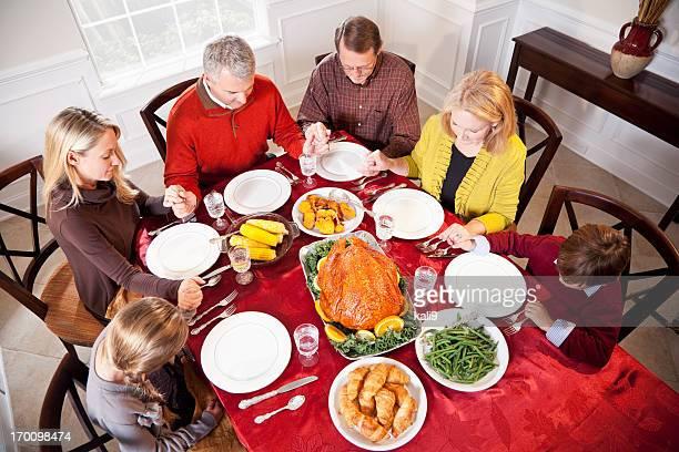 Multi-ethnischen Familie sagen Gebete vor dem Feiertag Abendessen