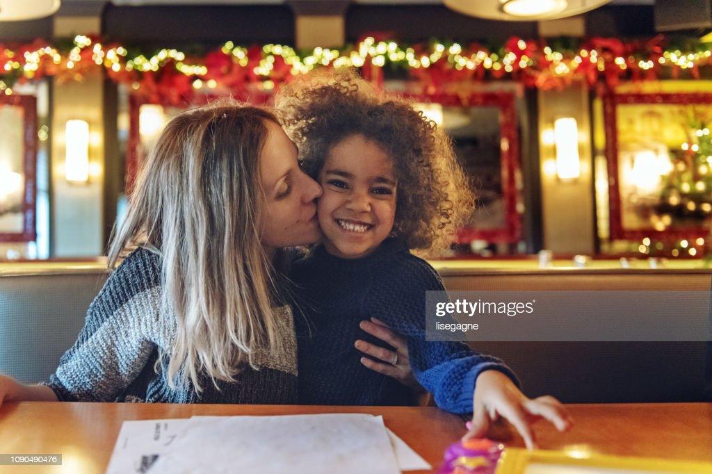 Multi-ethnic family shopping for Christmas, having a break in a restaurant : Stock Photo