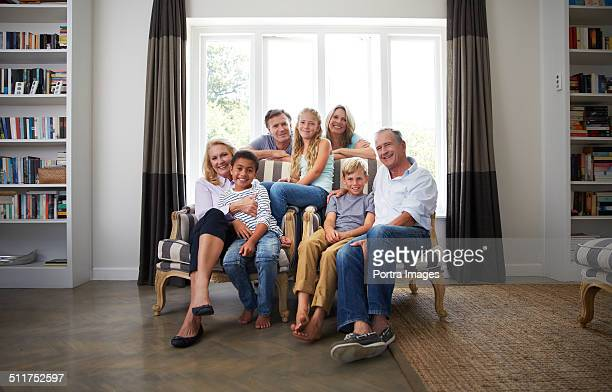 Multi-ethnic family smiling in house