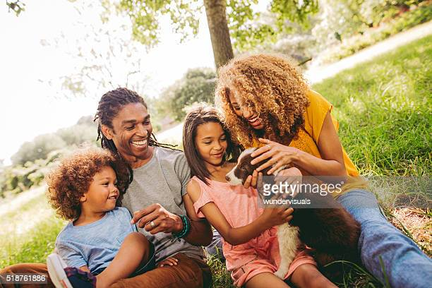 Multi-ethnic family spending time at park with new adorable pet