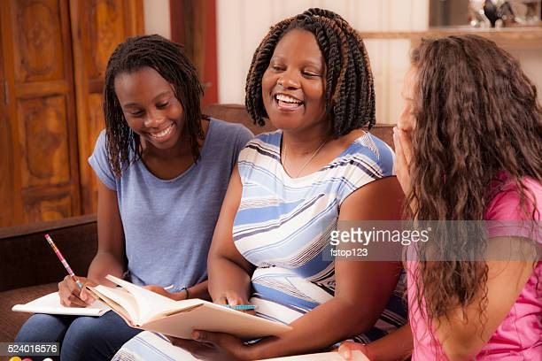 Multi-ethnic family.  Teenage girls and mom at home laughing.