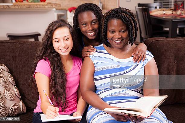 multi-ethnic family.  teenage girls and mom at home studying, laughing. - stepfamily stock photos and pictures