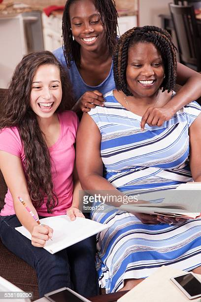 Multi-ethnic family.  Teenage girls and mom at home studying, laughing.