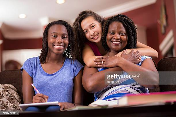 Multi-ethnic family.  Teenage girls and mom at home studying, talking.