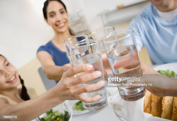multi-ethnic family toasting with water - trinkwasser stock-fotos und bilder