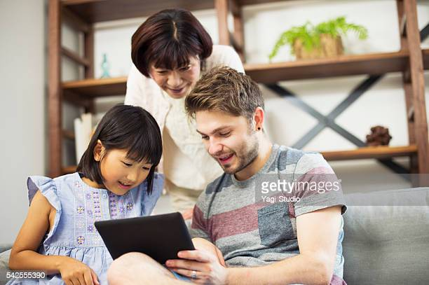 Multi-Ethnic family using digital tablet at home.