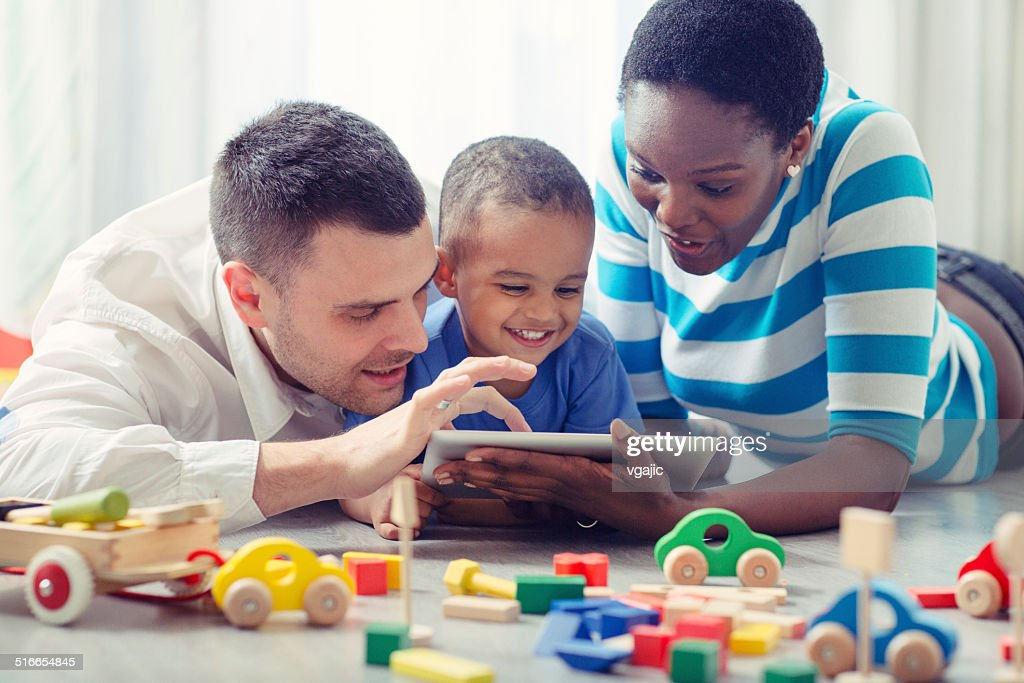 Multi-ethnic Family with one child having fun with digital tablet. : Stock Photo