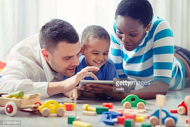Multi-ethnique Famille avec un enfant s'amusant avec tablette numérique.