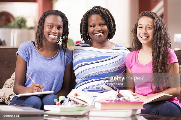 Multi-ethnic family with teenage girls and mom at home studying.
