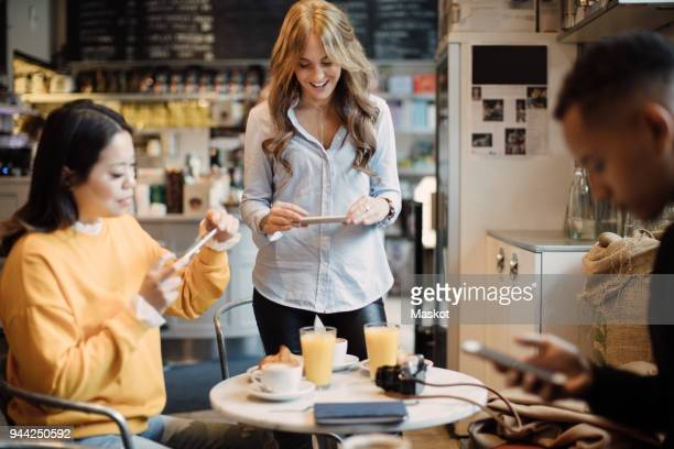 multi-ethnic female bloggers photographing food on table at cafe - influencer photos stock photos and pictures