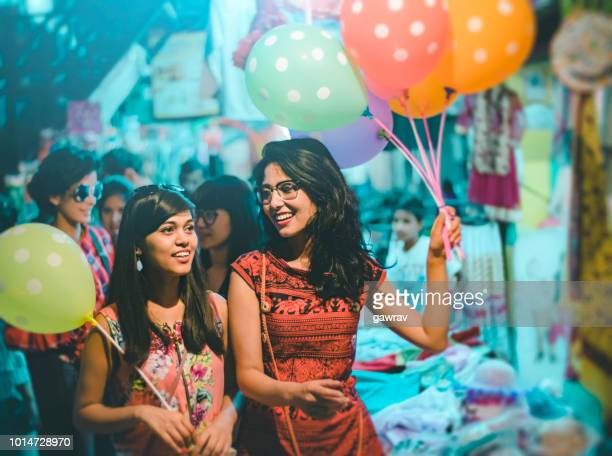 multiethnic female friends do fun in fair. - india market stock photos and pictures