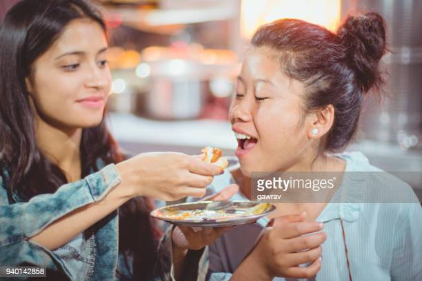 Multiethnic female friends eating fast food.