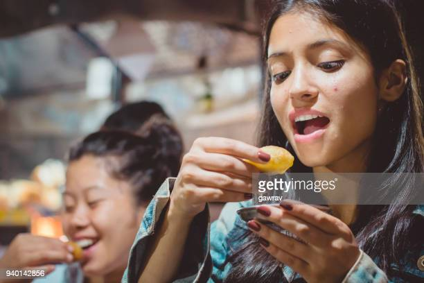 Multiethnic female friends eating pani puri.
