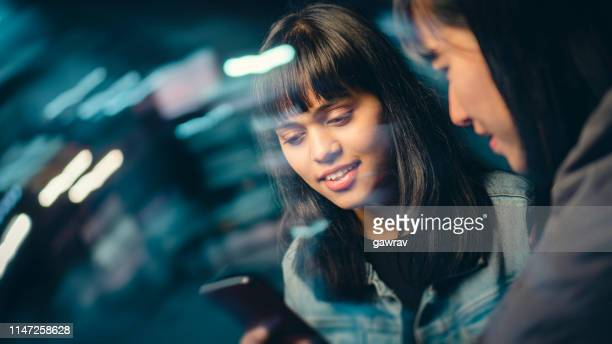 multiethnic female friends share smartphone on city street at night. - differential focus stock pictures, royalty-free photos & images
