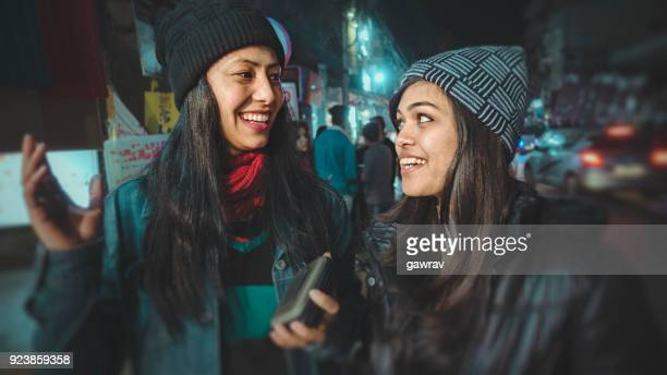 multi-ethnic female friends taking a walk together in market. - winter coat stock pictures, royalty-free photos & images