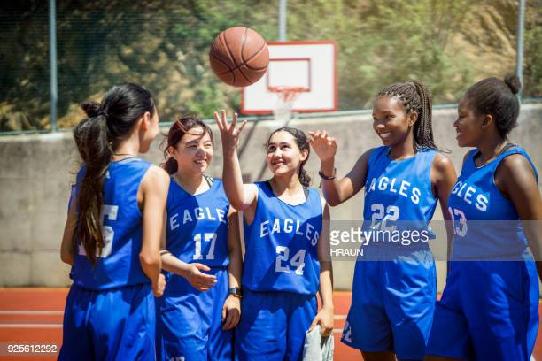 multi-ethnic female players throwing ball on court - basketball team stock pictures, royalty-free photos & images