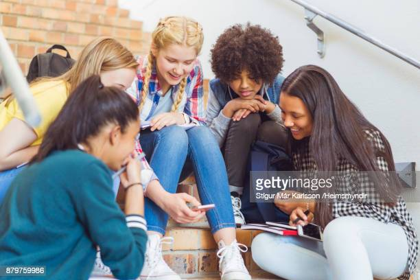multi-ethnic female students sharing mobile phone - teenagers only stock pictures, royalty-free photos & images