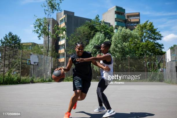multi-ethnic females playing streetball on court - women's basketball stock pictures, royalty-free photos & images