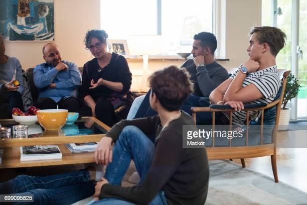 multi-ethnic friends and family talking while sitting in living room - fugitive stock photos and pictures