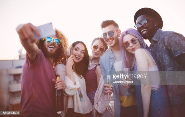 Multi-ethnic friends celebrating and taking a selfie at summer party