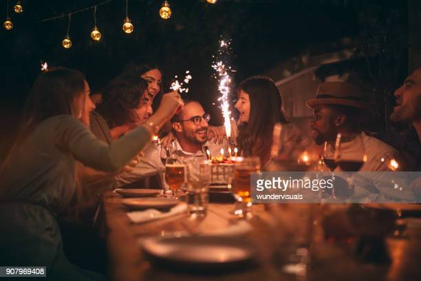 Multi-ethnic friends celebrating birthday and singing at rustic dinner party