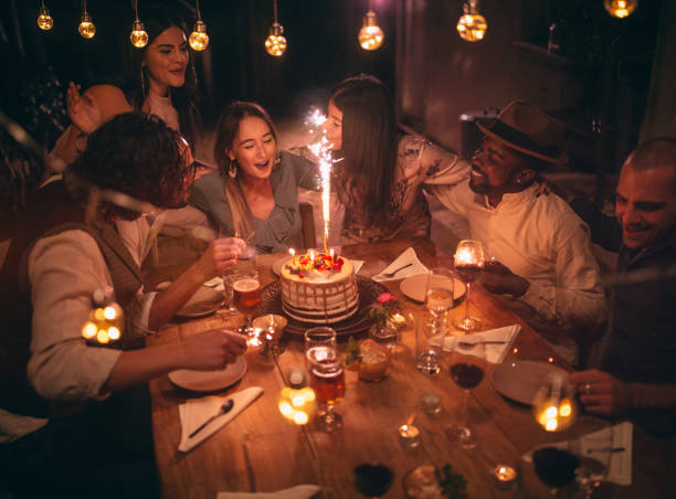 multi-ethnic friends celebrating birthday at rustic cottage dinner party - best friend birthday cake stock pictures, royalty-free photos & images