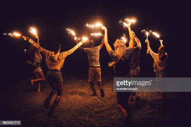 Multi-ethnic friends celebrating with sparklers at night on the beach