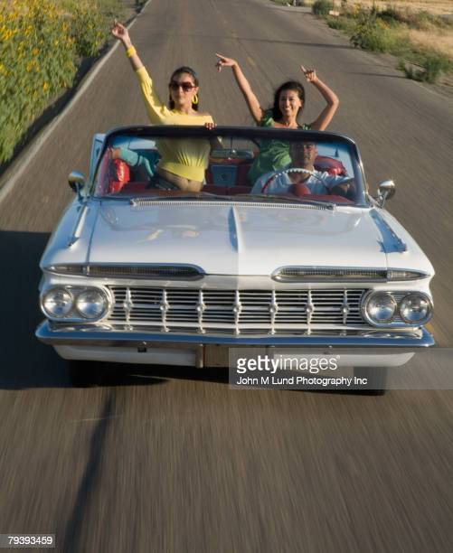 Multi-ethnic friends driving in low rider car