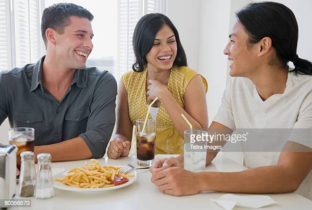 Multi-ethnic friends eating at diner