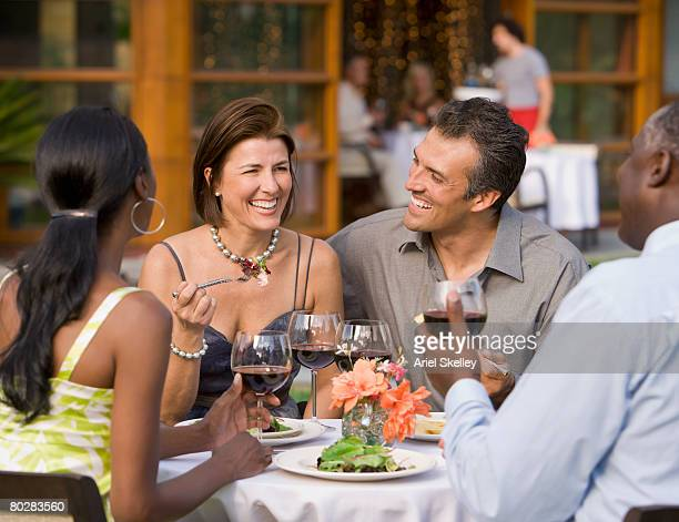 Multi-ethnic friends eating outdoors
