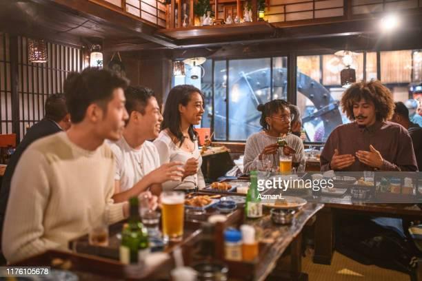 multi-etnische vrienden genieten van een goed verhaal in tokyo izakaya - na werktijd stockfoto's en -beelden