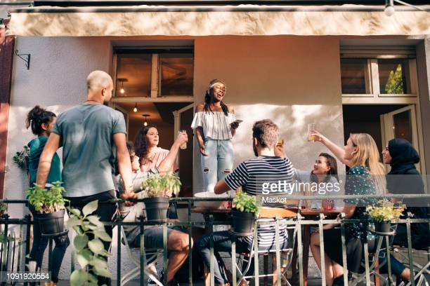 multi-ethnic friends enjoying at balcony during party - バルコニー ストックフォトと画像