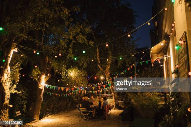 multi-ethnic friends enjoying dinner party in illuminated backyard - verlicht stockfoto's en -beelden