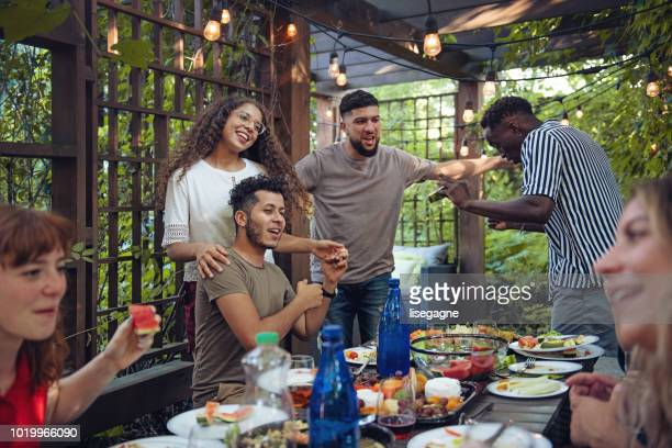 multi-ethnic friends enjoying dinner together - backyard party stock pictures, royalty-free photos & images
