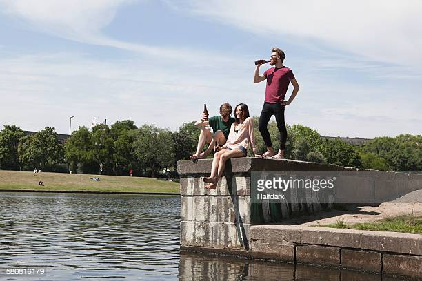 multi-ethnic friends enjoying on retaining wall by canal - men friends beer outside stock pictures, royalty-free photos & images