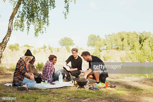 Multi-ethnic friends enjoying picnic at lakeshore