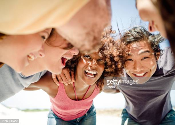 Multi-ethnic friends forming huddle at beach