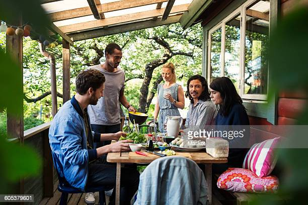 Multi-ethnic friends having food on porch at log cabin during summer party