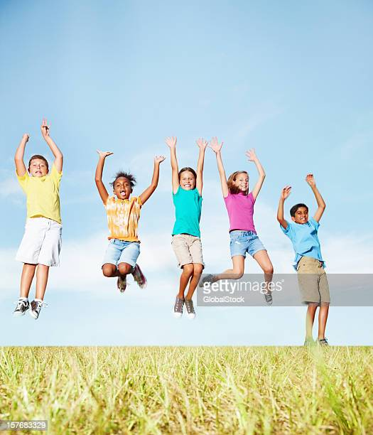 Multi-ethnic friends having fun while jumping against sky
