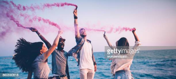 Multi-ethnic friends having fun with smoke bombs by the sea