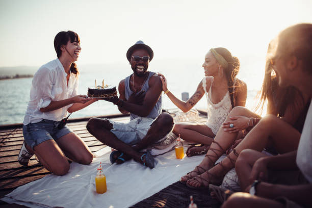 multi-ethnic friends having surprise birthday party on jetty in summer - best friend birthday cake stock pictures, royalty-free photos & images