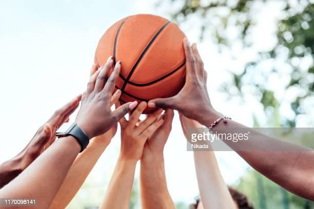 multiethnische freunde, die basketball halten - basketball stock-fotos und bilder