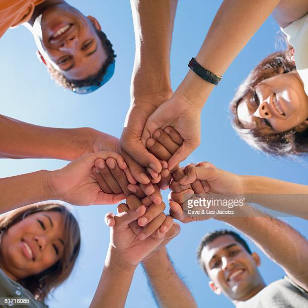multi-ethnic friends holding hands in huddle - dedication stock pictures, royalty-free photos & images